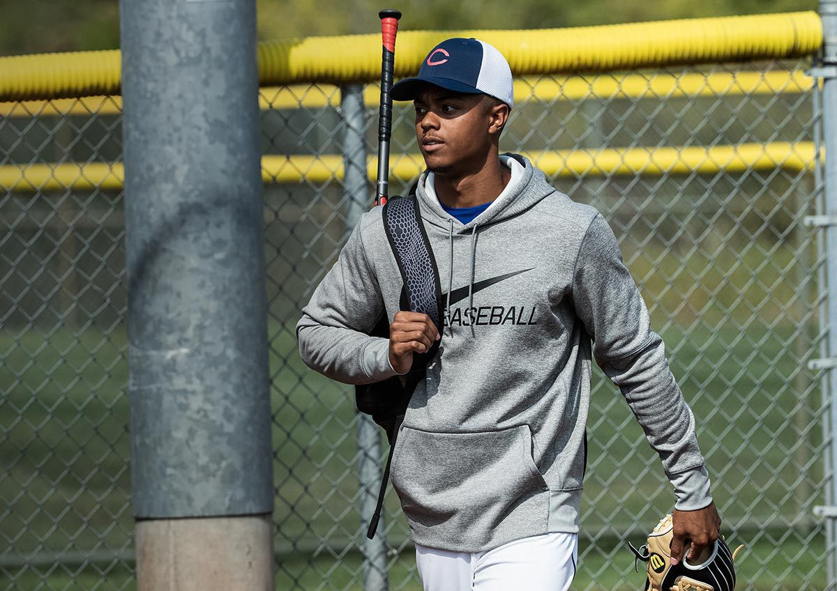 A young man walking next to a baseball field with baseball gear, wearing a Nike Men's Pullover Baseball Hoodie.