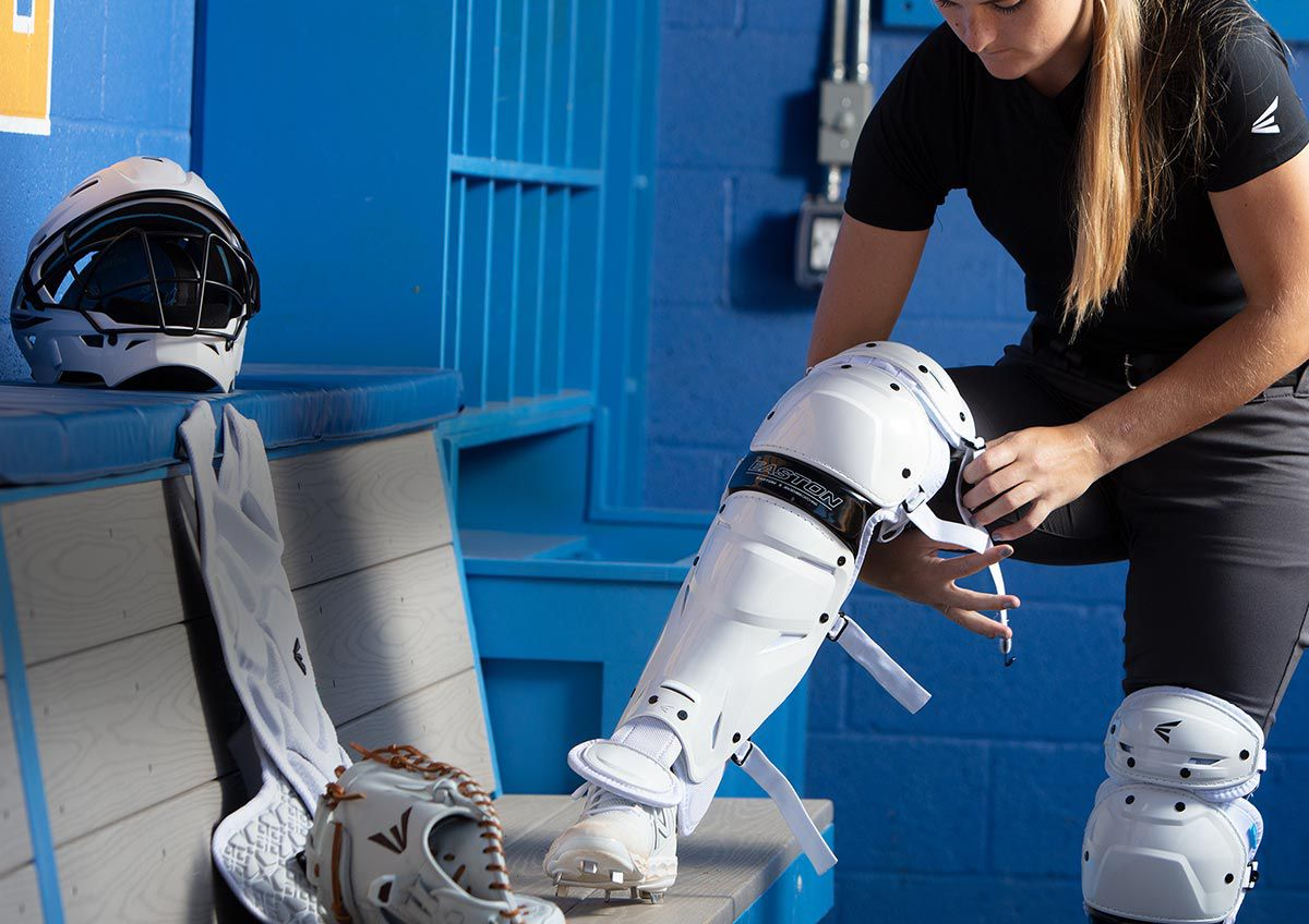 A girl suiting up in the Easton Jen Schro ''The Very Best'' Fastpitch Catcher's Set 2020.