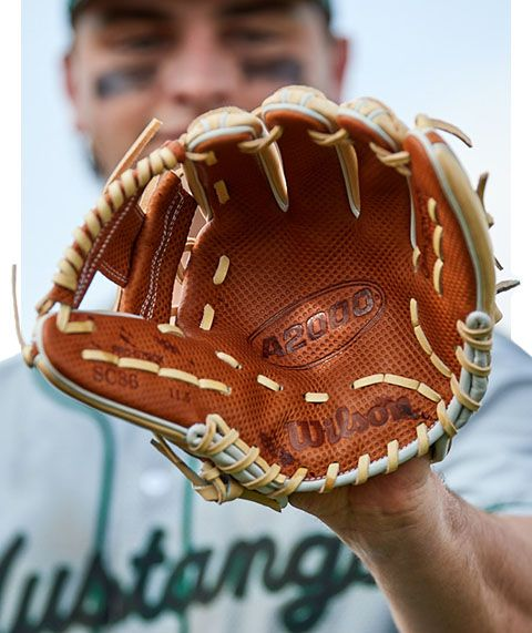 A player holds the Wilson A2000 glove up to the camera.