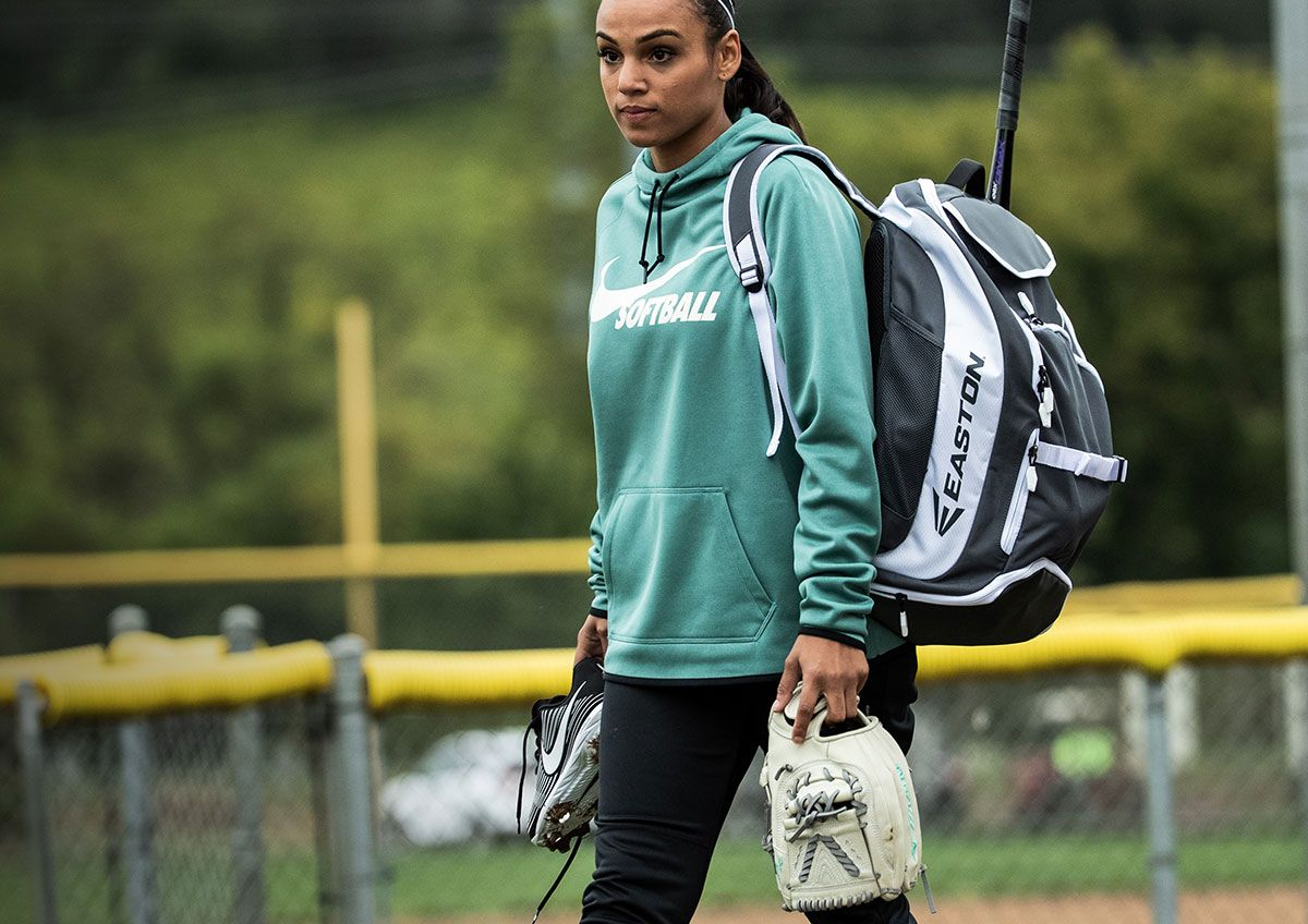 A young woman on a baseball field carrying her baseball gear, wearing a Nike Women's Therma Pullover Softball Hoodie.