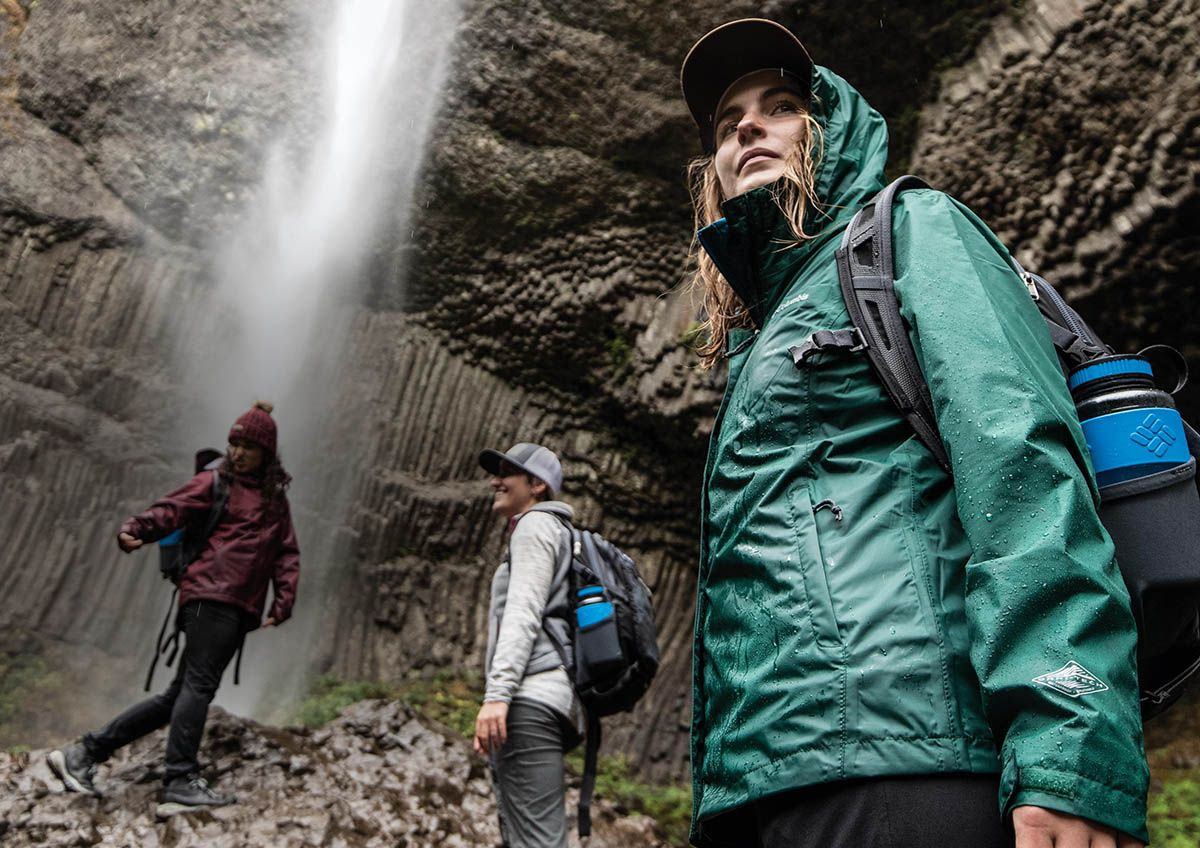 Three people hiking at the base of a waterfall wearing Columbia gear.