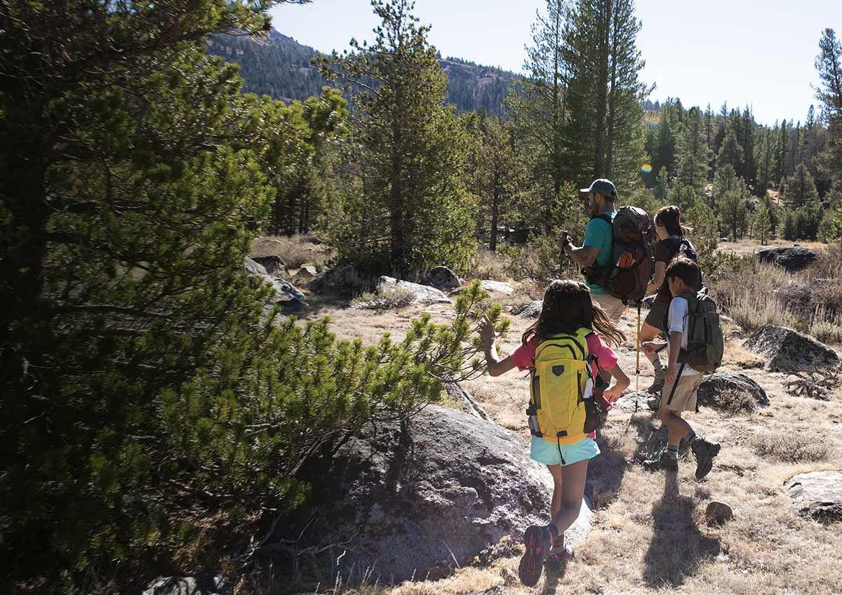 A family hikes in a semi-arid environment.