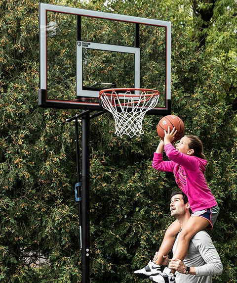 A girl on her dad's shoulders takes a shot at a new basketball hoop.