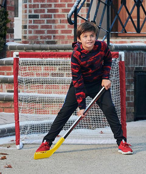 A boy stands in front of a street hockey goal.