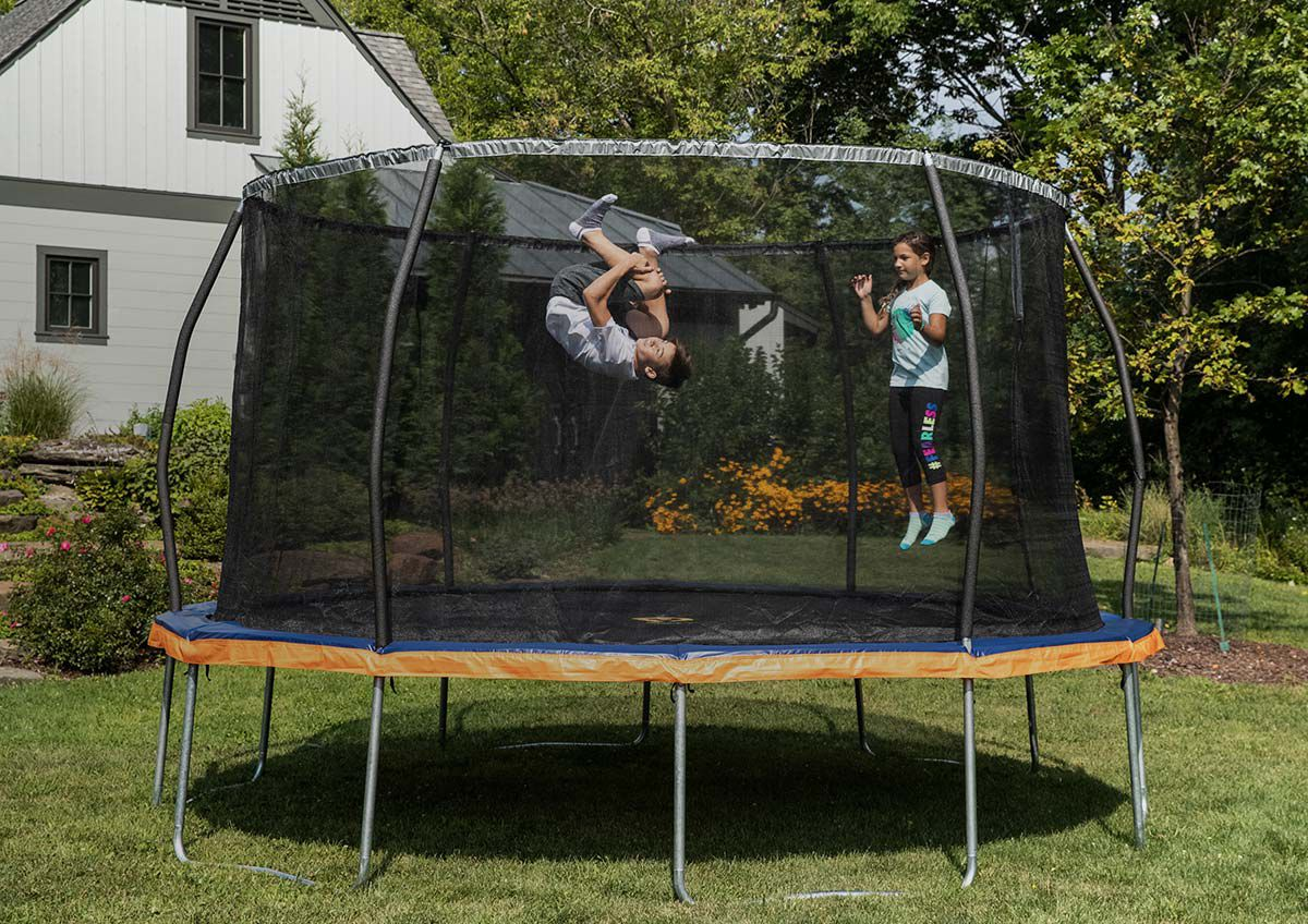 An image of two children playing in an enclosed trampoline the back yard, simultaneously in midair on a beautiful sunny day.
