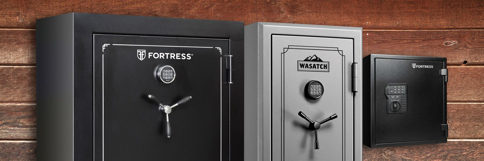 Image shows multiple gun safes in front of a wood panel background.