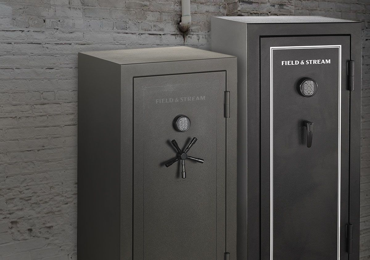 Two various size Field & Stream safes, in both sportsman and pro styles, placed against a white-washed brick wall.