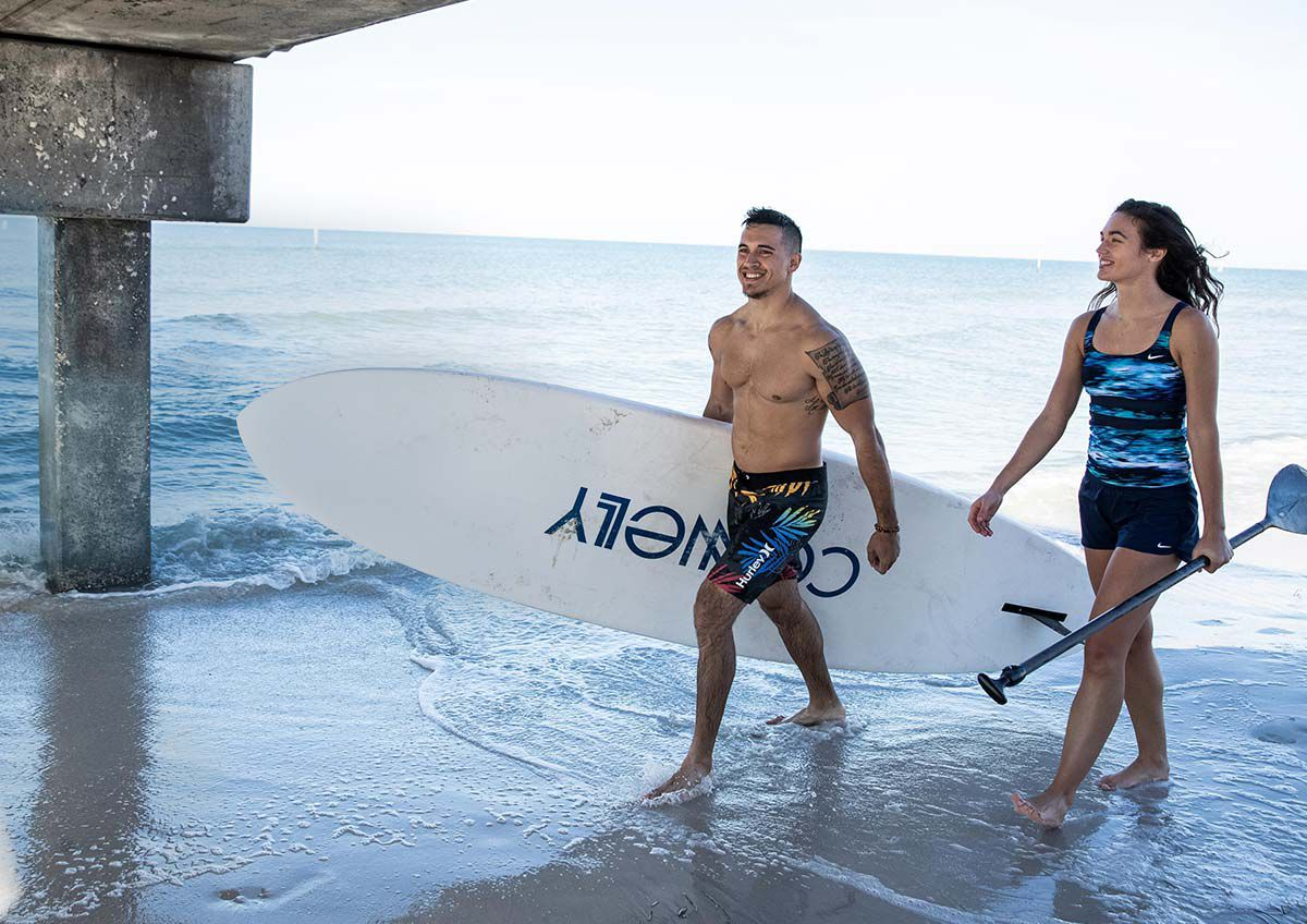 A man and woman walking on a beach, carrying a paddle board and paddle.