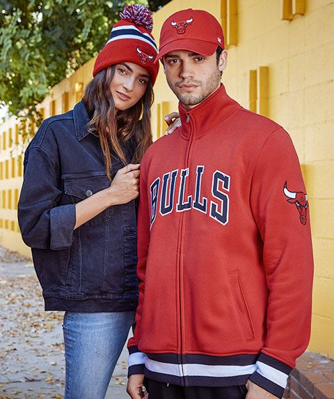 A woman wearing a Chicago Bull's pom-beanie next to a man wearing a Chicago Bull's full-zip sweatshirt and a Chicago Bull's brimmed cap.
