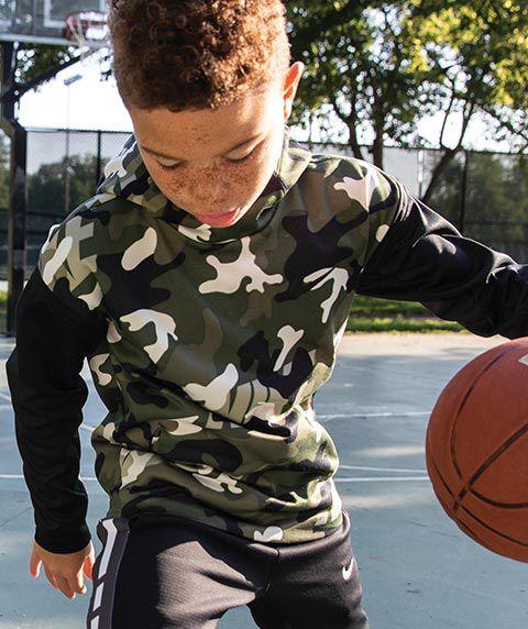 A kid playing basketball wearing Nike Boys' Therma Camo Printed Hoodie, Nike Boys' Dri-FIT Therma Elite Pants and Nike Kyrie Flytrap II Basketball Shoes.