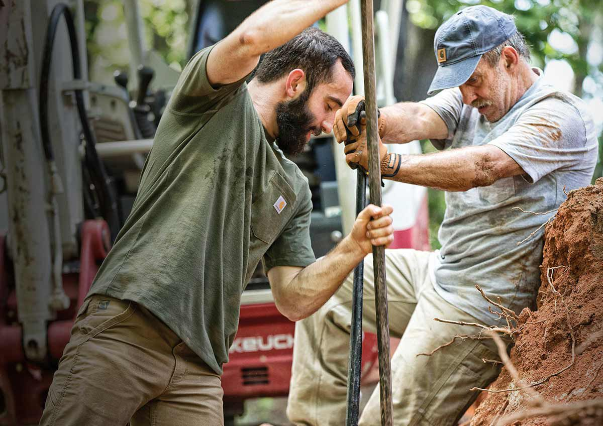 Two men working hard in the yard.