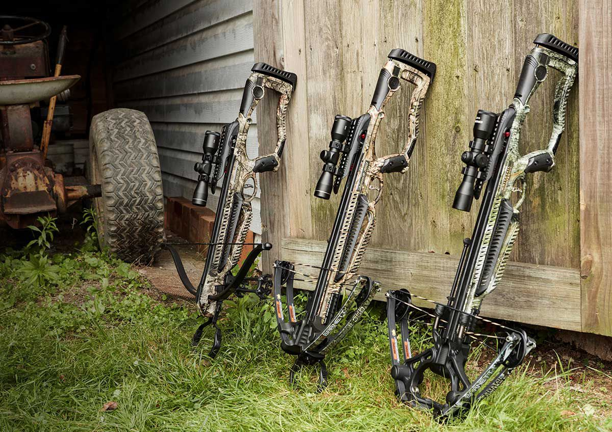 Three Barnett crossbow models, lined up side by side against a wooden barn door, next to a vintage tractor.