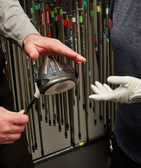 A Picture Of A Golf Pro Holding A TaylorMade SIM Golf Club