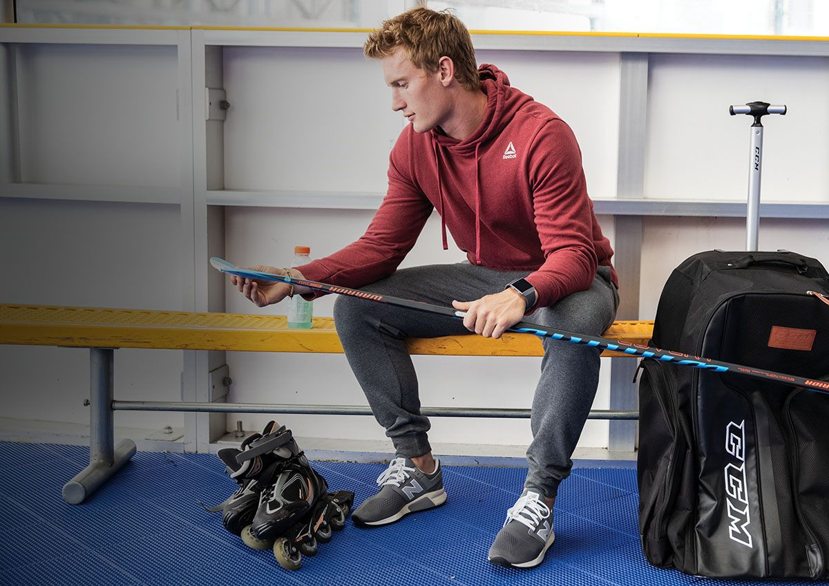 A young man prepares his gear to play roller hockey.