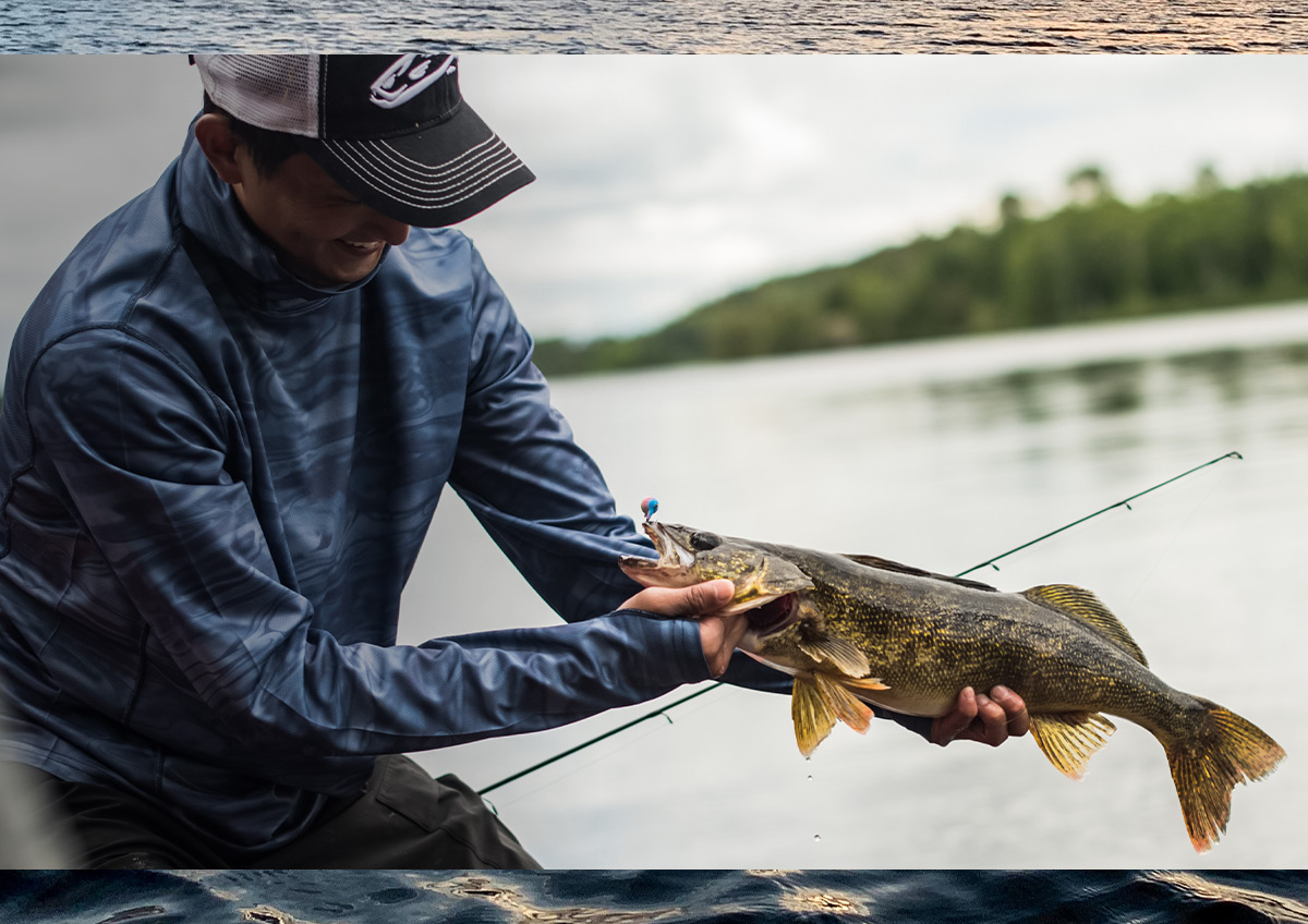 A male fisherman holding his latest catch: a walleye.