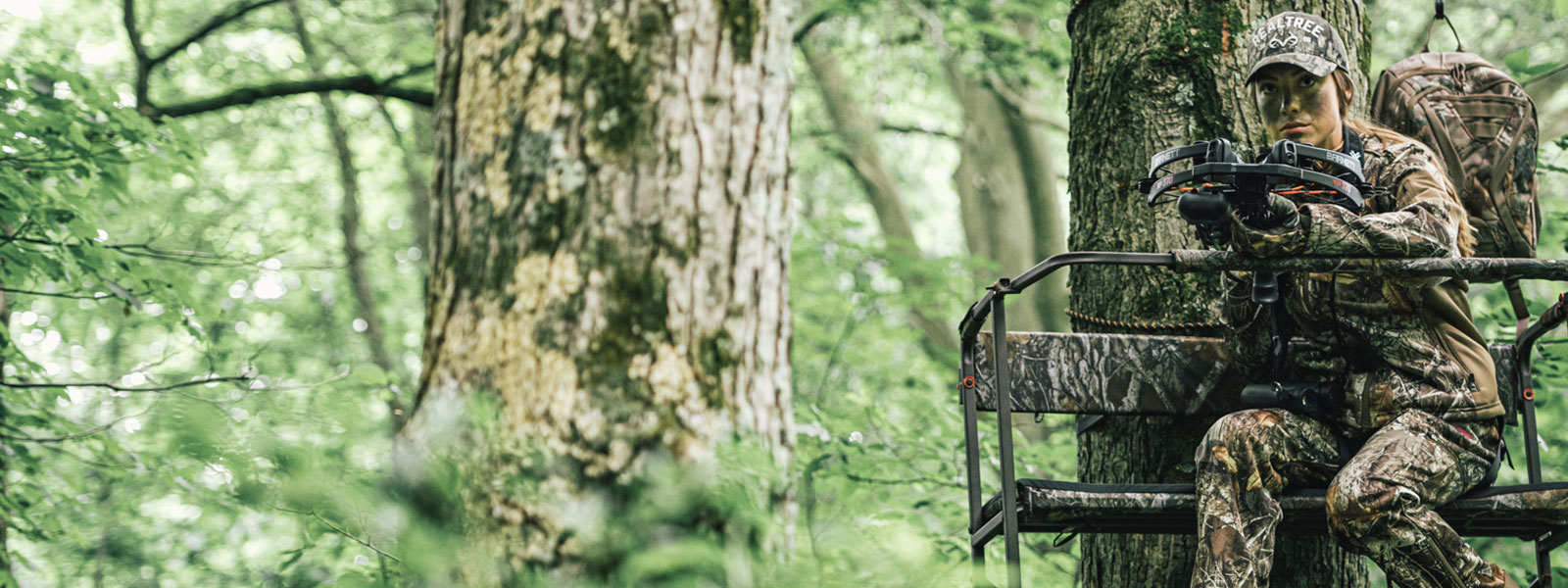 A female hunter wearing camouflage hunting apparel looks out from her ladder stand while holding a crossbow.
